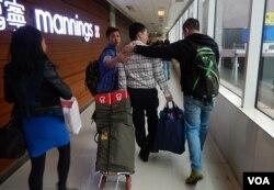 中國旅客李先生與太太(拖購物車者)一度被反水貨客示威者包圍,由便衣警員護送離開。(美國之音湯惠芸攝)