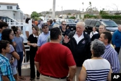 President Donald Trump and Puerto Rico Governor Ricardo Rosselló, center, listen to residents and survey hurricane damage and recovery efforts in a neighborhood in Guaynabo, Puerto Rico, Tuesday, Oct. 3, 2017.