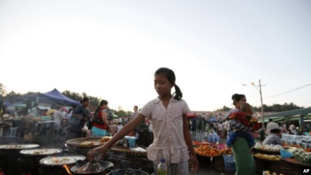 A girl cooks snacks to sell in Myoma market at Naypyitaw, Burma, December 18, 2011.