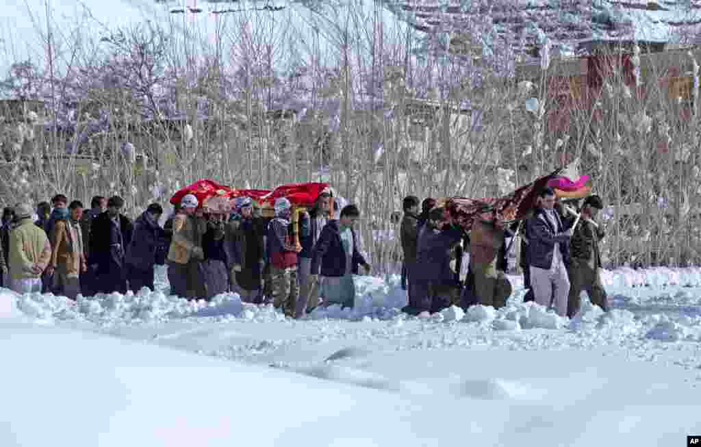 Afghan villagers carry the bodies of victims of an avalanche, in the Khanj district of Panjshir province, north of Kabul, Feb. 26, 2015.