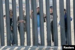 امریکہ میں داخل کے خواہش مند تارکین وطن میکسیکو سرحد کلی دیوار کی دوسری جانب سے امریکی سرزمیں کو حسرت سے دیکھ رہے ہیں۔ 18 نومبر 2018