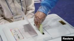Seorang pemilih mengenakan sarung tangan plastik memasukkan surat suara di tempat pemungutan suara dalam pemilu legislatif di tengah pandemi virus corona di Seoul, Korea Selatan, 15 April 2020. (Foto: Reuters)