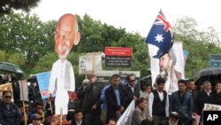 Protesters with a cutout of Afghan President Ashraf Ghani demonstrate against his visit to Australia outside Government House where Ghani met with Governor-General Peter Cosgrove, in Canberra, April 3, 2017.