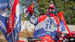 FILE - A supporter of the New Patriotic Party (NPP) wears campaign paraphernalia on the side of a road in Accra, Ghana, Nov. 23, 2012. The NPP won its challenge to qualify a candidate for the December 7 presidential election.