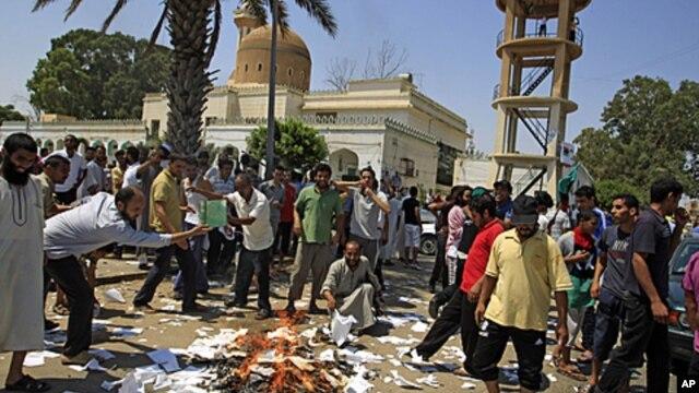 Rebel supporters burn copies of Gadhafi's 'Green Book' in the main square of the Qasr Bin Ghashir district in Tripoli, Libya, August 27, 2011
