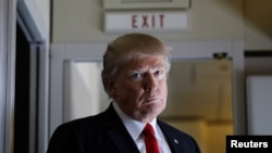 Presiden AS Donald Trump berbicara dengan wartawan di atas pesawat kepresidenan Air Force One dalam penerbangan menuju Palm Beach, Florida (3/2). (Reuters/Carlos Barria)