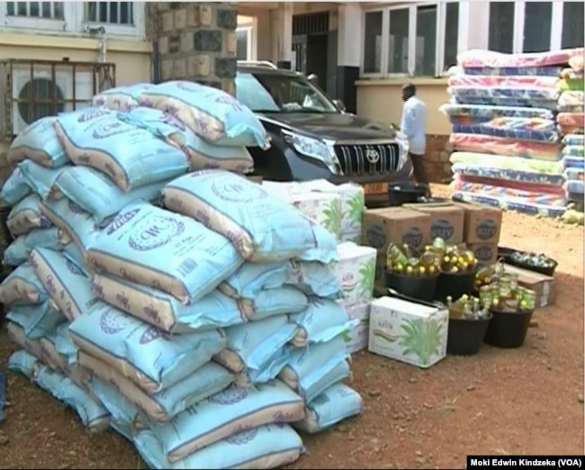 Piles of food aid, left, and mattresses, right, are distributed to internally displaced people in the English-speaking town of Bamenda, April 3, 2019.