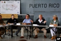 President Donald Trump and first lady Melania Trump participate in a briefing on hurricane recovery efforts with first responders at Luis Muniz Air National Guard Base, Tuesday, Oct. 3, 2017, in San Juan, Puerto Rico
