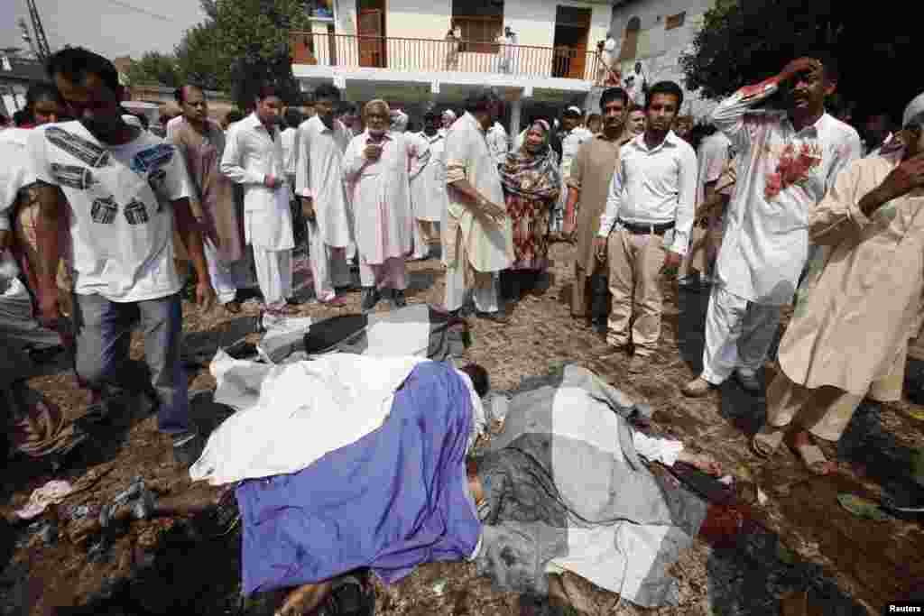 People gather around dead bodies at the site of a suicide blast at a church in Peshawar, Pakistan, Sept. 22, 2013.