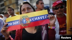 A supporter of Venezuelan President Hugo Chavez attends a gathering outside Miraflores Palace in Caracas, January 10, 2013.