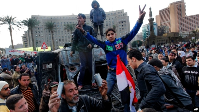 Egyptian protesters celebrate the capture of a state security armored vehicle that demonstrators commandeered during clashes with security forces and brought to Tahrir Square in Cairo, January 29, 2013.