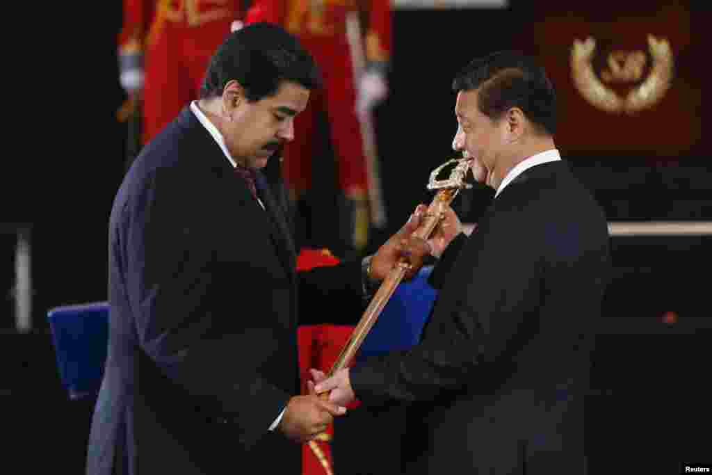 Venezuelan President Nicolas Maduro, left,  presents Chinese President Xi Jinping with a replica of the sword of national hero Simon Bolivar during a ceremony at the National Pantheon in Caracas, July 20, 2014.