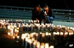 2015年10月1日罗斯伯格居民为乌姆普夸社区大学举行烛光祈祷会后,人们用蜡烛组成了该校的缩写字母,悼念无辜受害的死者。