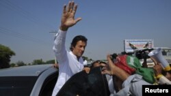 Politisi Imran Khan (tengah) melambai kepada para pendukungnya saat memimpin protes anti serangan misil AS di Pakistan (7/10).