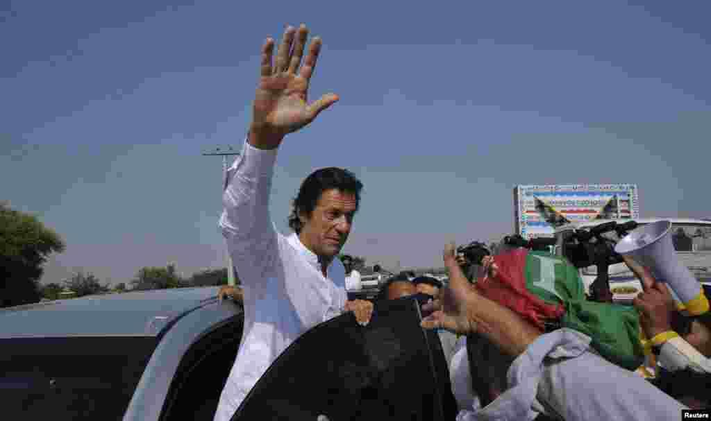 عمران خان ہاتھ ہلا کر شرکاء کا جواب دے رہے ہیں