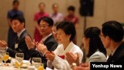 한국의 박근혜 대통령이 30일 오후 시안 샹그릴라호텔에서 열린 한국인 오찬 간담회에서 중국 방문을 축하하며 박수치고 있다.