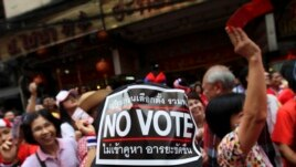 "An anti-government supporter wearing a cap with a ""No vote"" sticker attends a march through China Town in Bangkok, Feb. 1, 2014."
