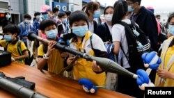 """香港小学生在2021年4月15日的""""全民国家安全教育日""""展览上拿起仿造的榴弹发射器"""