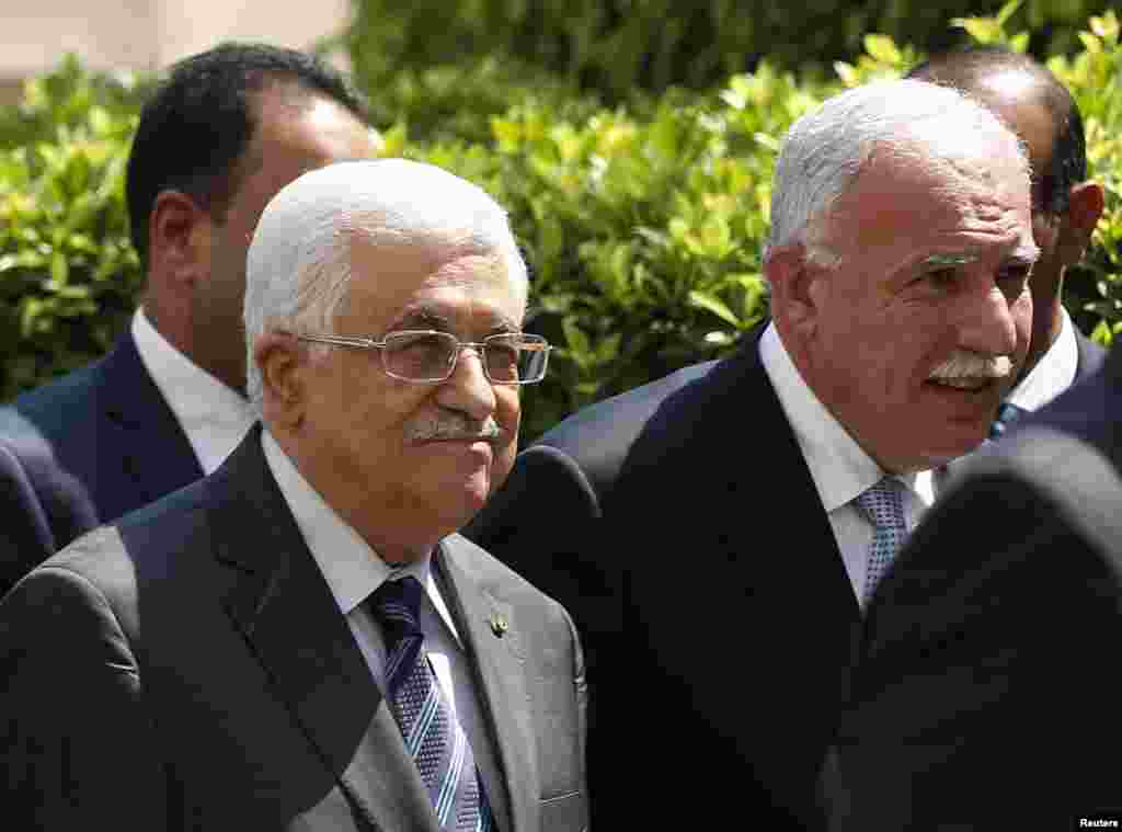 Palestinian President Mahmoud Abbas and his foreign minister Riyad al-Maliki, right arrive for an Arab League Foreign Ministers emergency meeting at the league's headquarters in Cairo, Sept. 7, 2014.