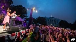 바락 오바마(무대 위 오른쪽) 미국 대통령이 부인 미셸 여사와 함께 지난해 백악관에서 진행된 독립기념일 행사에서 연설하고 있다.
