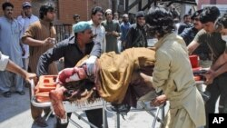 A man, who was injured in a bomb blast, is wheeled on a stretcher to a hospital, in Peshawar, Pakistan, June 8, 2012.