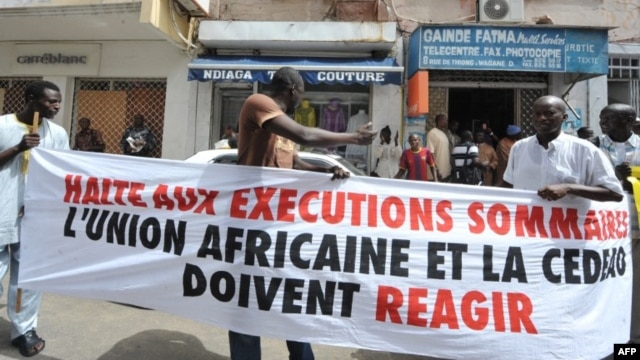 "Protesters gather outside the Gambian Embassy in Senegal on August 30, 2012. The banner reads: "" Stop summary executions. The African Union and ECOWAS must react."""