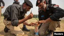Technicians from Pakistan's top bomb disposal unit prepare an improvised detonator to demonstrate how to destroy militant bombs at the unit's headquarters in Peshawar, September 12, 2013.