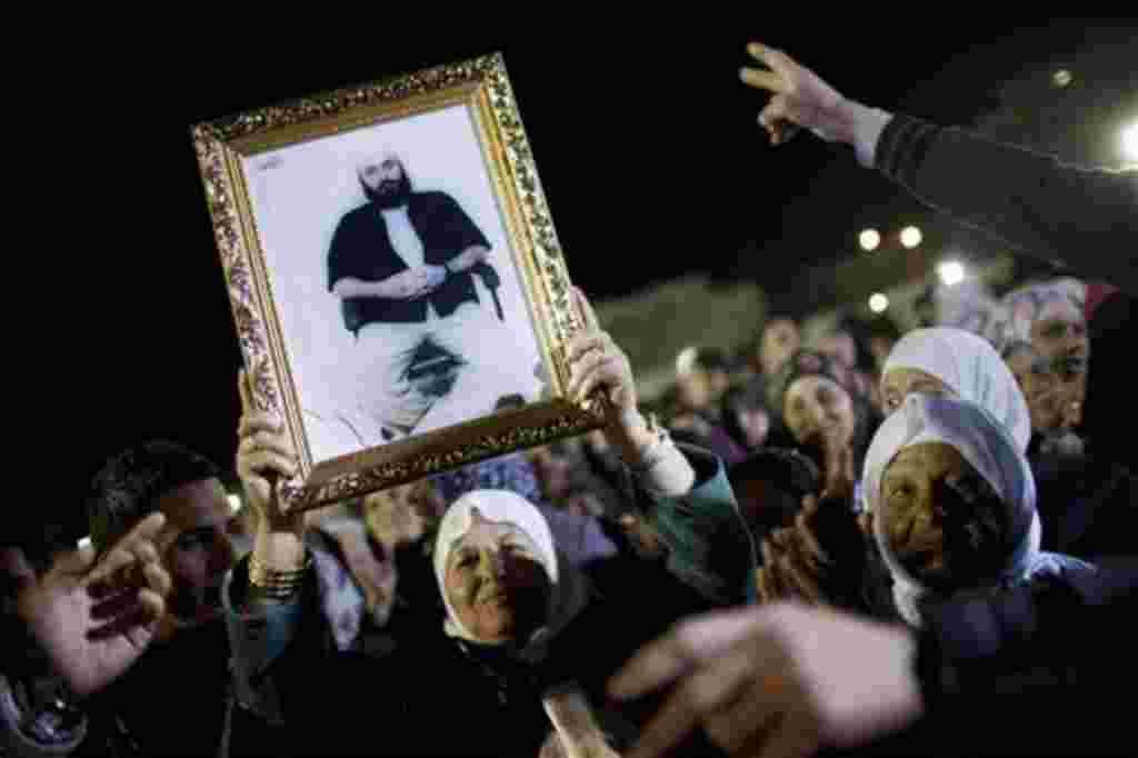 Una mujer palestina con la foto de sus familiares minutos antes de que fueran liberados los prisioneros palestinos en complejo presidencial de Ramallah, en Cisjordania.