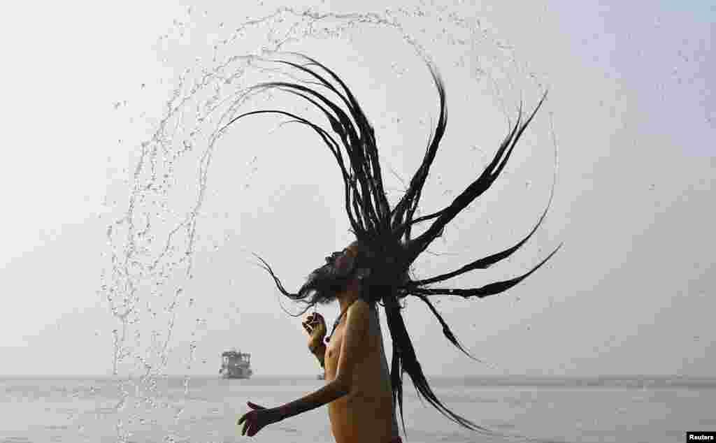 """Orang suci Hindu atau """"Sadhu"""" mandi di sungai Gangga menjelang festival keagamaan """"Makar Sankranti"""" di Pulau Sagar, dekat Kolkata, India."""
