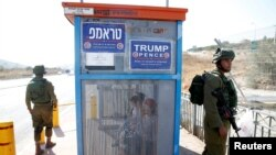 Israeli soldiers stand near a bus stop featuring posters from the Israeli branch of the U.S. Republican party campaign in support of Donald Trump, Oct. 6, 2016.