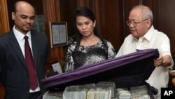 This photo provided by the Bangko Sentral ng Pilipinas, from left, Second Secretary and Head of Chancery of the Bangladesh Embassy in Manila Probash Lamarong, Anti-Money Laundering Council (AMLC) Secretariat Executive Director Julia Bacay-Abad
