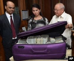 This photo provided by the Bangko Sentral ng Pilipinas, from left, Second Secretary and Head of Chancery of the Bangladesh Embassy in Manila Probash Lamarong, Anti-Money Laundering Council (AMLC) Secretariat Executive Director Julia Bacay-Abad and AMLC Member and Insurance Commissioner Emmanuel Dooc opens a bag containing US dollars that was returned by Chinese casino junket operator Kam Sin Wong to Bangladesh and Philippine AMLC officials in Manila, March 31, 2016.