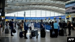 在英國倫敦希斯羅機場排隊等待乘機的旅客。 (資料圖片)