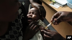 Ảnh tư liệu - Một người mẹ ôm con khi tiêm vắc xin sốt rét tại Trung tâm Nghiên cứu Dự án Walter Reed ở Kenya, ngày 30 tháng 10 năm 2009.