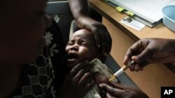 A mother holds her baby as she receives a new malaria vaccine at the Walter Reed Project Research Center in Kenya, October 30, 2009.