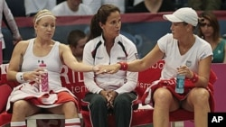 Bethanie Mattek-Sands, left, of the United States touches hands with doubles partner Liezel Huber as they talk with coach Mary Joe Fernandez during their doubles match against Russia in their Fed Cup tennis match in Birmingham, Ala., 25 Apr 2010 (file pho