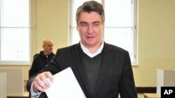 PM Kroasia, Zoran Milanovic memasukkan kartu suara di sebuah TPS di ibukota Kroasia, Zagreb hari Minggu (8/11).