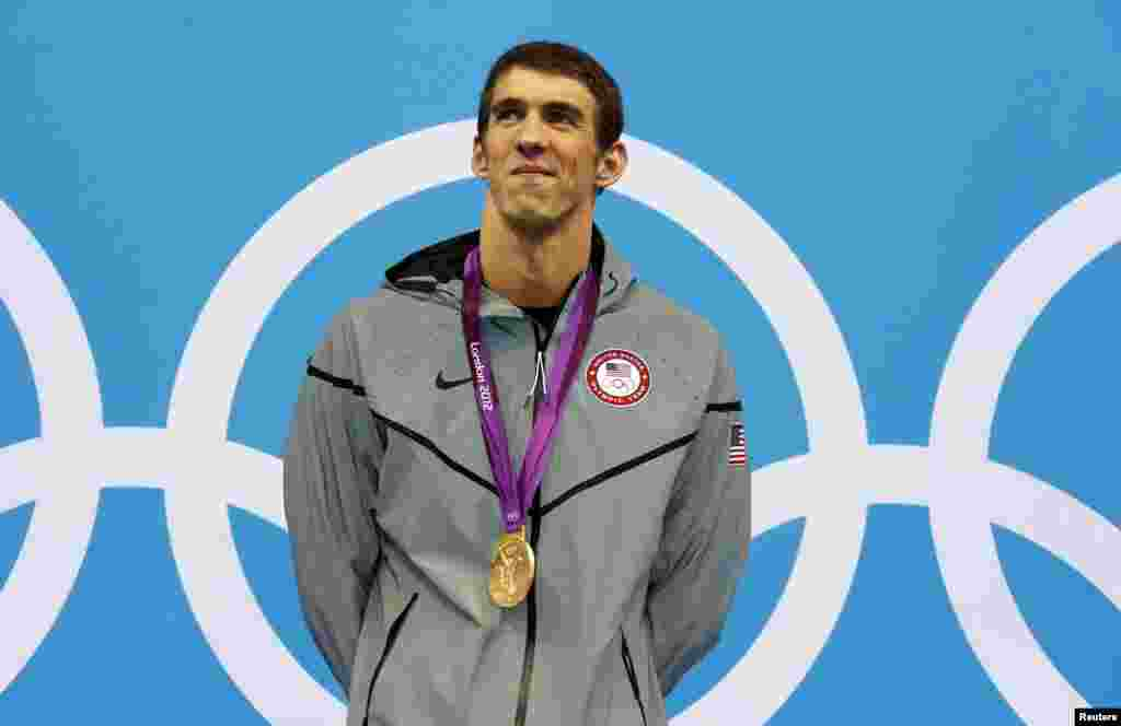 Michael Phelps of the U.S. smiles with his gold medal during the men's 200m individual medley victory ceremony during the London 2012 Olympic Games at the Aquatics Centre August 2, 2012.