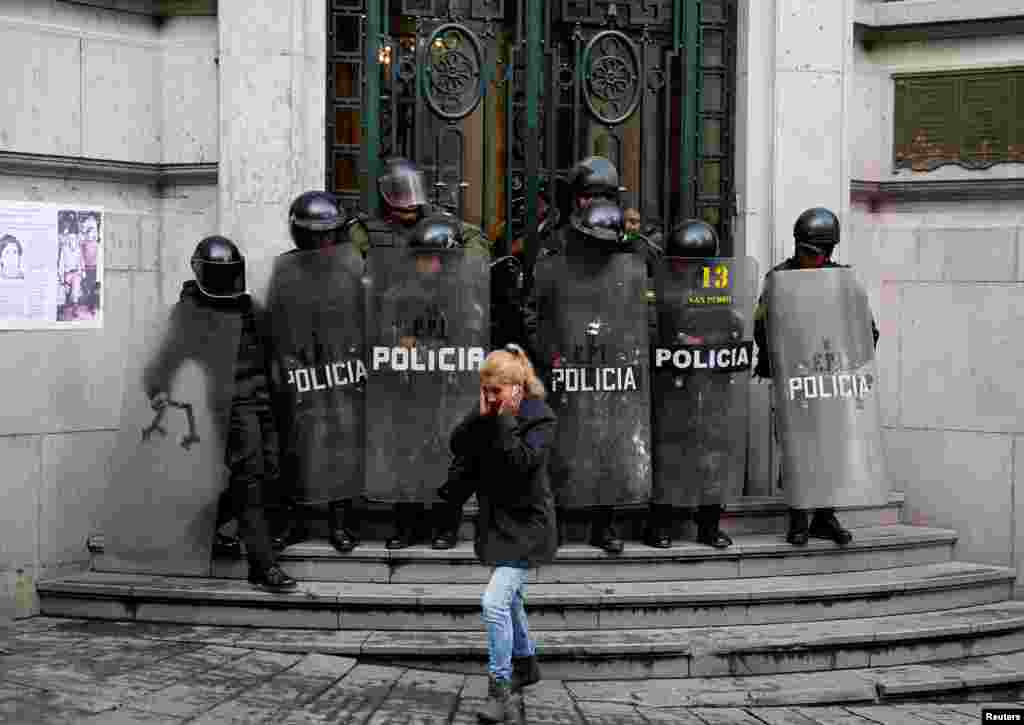 A pedestrian walks in front of riot policemen at the Bolivian Vice Presidency during a rally protest against Bolivia's government new health care policies in La Paz, Jan. 8, 2018.