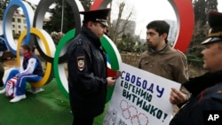 Activist David Khakim (C) is approached by two police officers after pulling out a banner protesting a recent prison sentence for a local environmentalist in front of the Olympic rings, Feb. 17, 2014, in central Sochi, Russia.