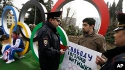 2月17日在索契奥运场地外,环保人士哈基姆(中)举牌抗议另一名环保活动人士被判刑