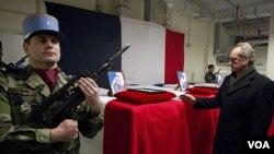 Menteri Pertahanan Perancis Gerard Longuet (kanan) berdiri di depan empat peti jenazah tentara Perancis di bandara Kabul (21/1).