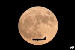 In this Nov. 14, 2016 photo, a jet plane flies across the moon which is at its brightest in almost 69 years.