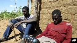 Zimbabweans listen to a radio for an announcement of election results in Umguza April 1, 2008 (file photo).