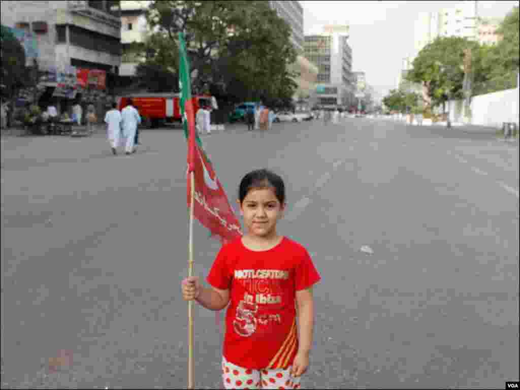 احتجاجی دھرنے سے قبل ایک بچی پارٹی جھنڈا اٹھائے ہوئے
