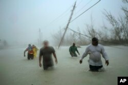 Volunteers walk under the wind and rain from Hurricane Dorian through a flooded road as they work to rescue families near the Causarina bridge in Freeport, Grand Bahama, Bahamas, Tuesday, Sept. 3, 2019.