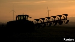 FILE - A French farmer drives a tractor as he ploughs a field in front of power-generating windmill turbines at a wind park in Vauvillers, in France, November 23, 2015. A new study counts farms among the biggest contributors to pollution.