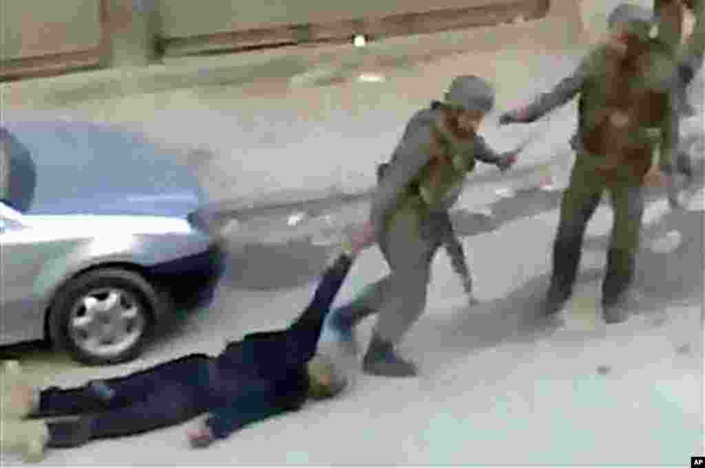 This image from amateur video shows government troops dragging a body away in Damascus, Syria, November 10, 2011. (AP)