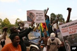 Zimbabweans celebrate following the resignation of President Robert Mugabe, in Harare, Zimbabwe, Nov, 21, 2017.