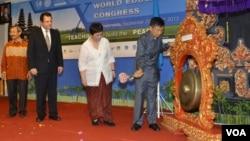 Gubernur Bali Made Mangku Pastika (kanan) memukul gong sebagai tanda dimulainya Kongres Pendidikan Dunia, diamati oleh Dubes RI untuk Argentina Nurmala Kartini Sjahrir (kedua dari kanan). (VOA/Muliarta)